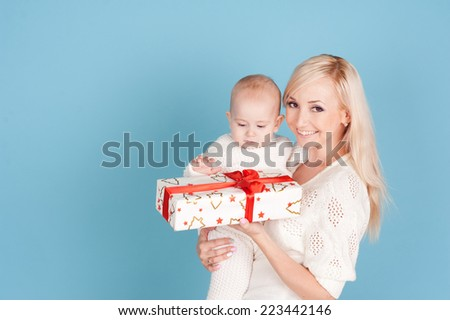 Smiling woman holding baby boy with christmas gift over blue. Happy family portrait - stock photo