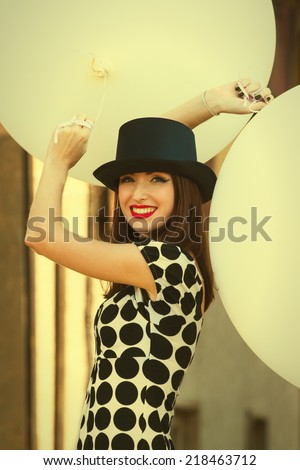 Smiling woman holding big white balloons. Fashion concept. Toned image