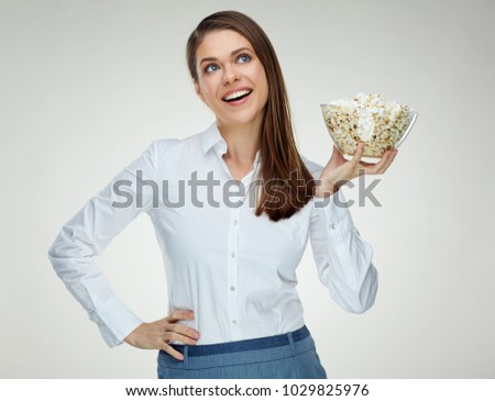 Smiling Woman  holding bowl with popcorn looking up. Isolated studio portrait.
