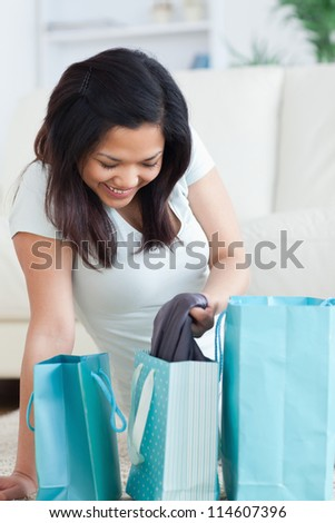 Smiling woman holding clothes from a shopping bag in a living room - stock photo