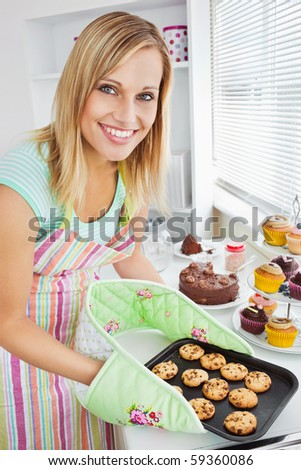 Smiling woman holding cookies in the kitchen at home - stock photo
