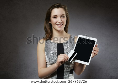 Smiling woman holding credit card and tablet - stock photo