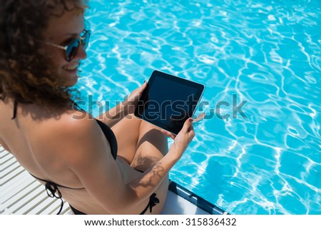 Smiling woman holding digital tablet with blank copy space screen for your information or content while sunbathing near hotel pool, female in black bikini working on touch pad while relaxing outside - stock photo