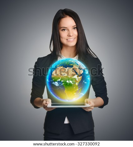 Smiling woman holding Earth globe over tablet. Elements of this image are furnished by NASA - stock photo