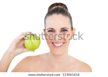 Smiling woman holding green apple looking at camera against white background