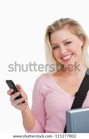 Smiling woman holding her cellphone and a novel against a white background - stock photo