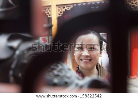 Smiling woman holding incense - stock photo