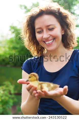 Smiling woman holding little yellow duckling in her hands - stock photo