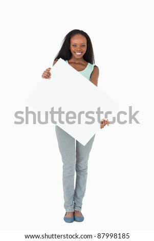 Smiling woman holding placeholder on white background - stock photo