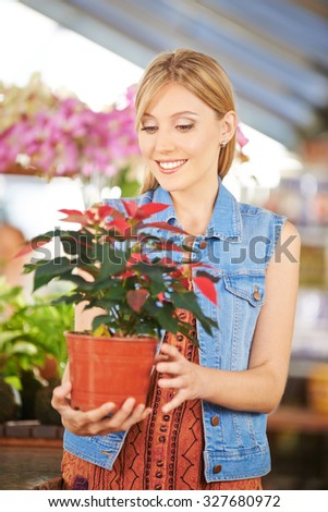 Smiling woman holding pot with poinsettia in a nursery - stock photo