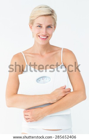Smiling woman holding scales looking at camera on white background - stock photo