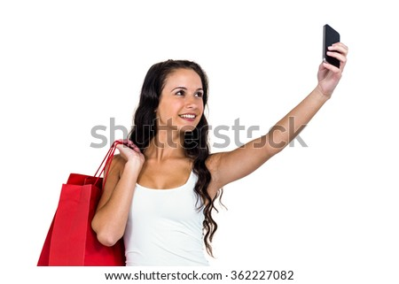 Smiling woman holding shopping bags taking selfie on white background