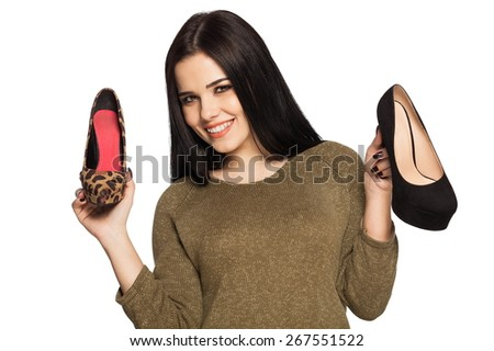 Smiling woman holding two shoes in her hands - shopping image. Gorgeous white caucasian female model isolated on white background.