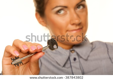 smiling woman holding up a key belonging to her house - stock photo
