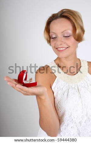 smiling woman holding wedding rings in red box - stock photo