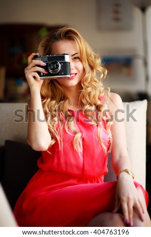 Smiling woman in a dress with a retro camera, on couch at home - stock photo