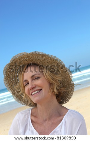 Smiling woman in a straw hat on the beach - stock photo