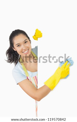 Smiling woman in apron and rubber gloves cleaning white surface - stock photo