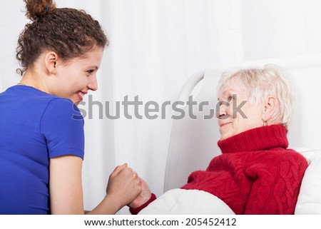 Smiling woman in bed and her granddaughter