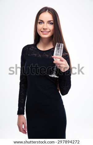 Smiling woman in black dress holding glass with champagne isolated on a white background. Looking at camera. Focus on glass - stock photo