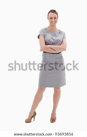 Smiling woman in dress with her arms folded against white background - stock photo