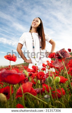 Smiling woman in field of poppy flowers - stock photo