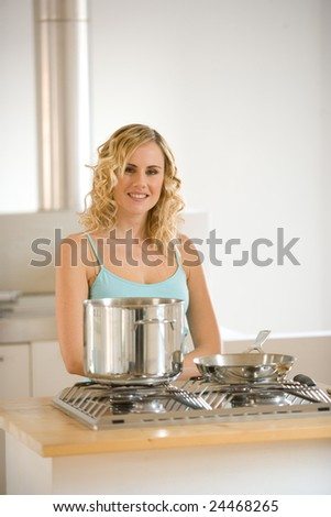 smiling woman in front of a kitchen - stock photo