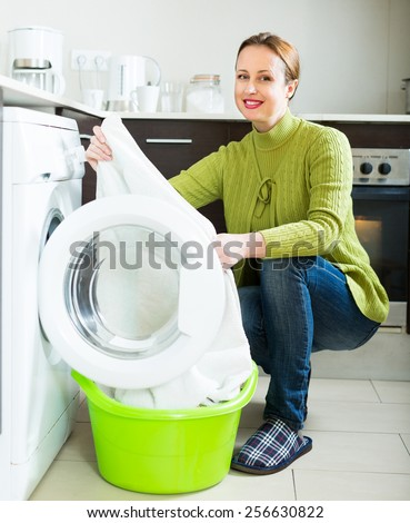 Smiling woman in green loading clothes into washing machine in home
