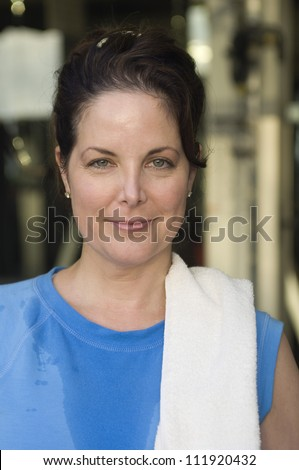 Smiling woman in gym with towel on her shoulder - stock photo