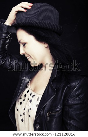 smiling woman in hat over dark background - stock photo