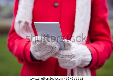 Smiling Woman in Red Coat and and wool cap and gloves read messages on smart phone and smiling. Urban Space. Cold Weather - stock photo