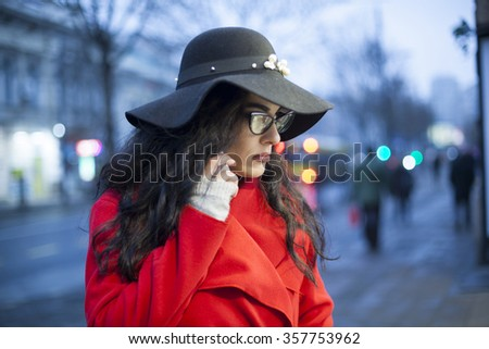 Smiling Woman in Red Coat and black hat and glasses, hold smartphone, Woman in red coat with smartphone in hands going through the city and looking shop windows. Urban Space, noise on image