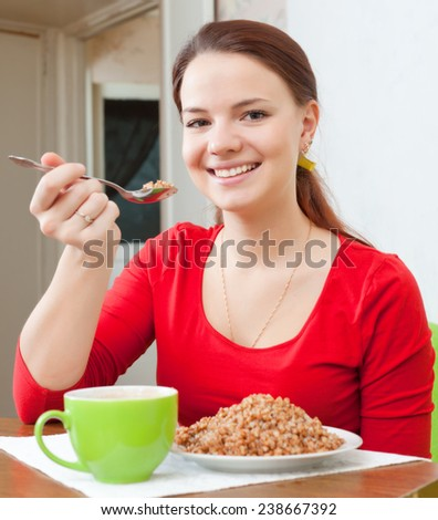 Smiling woman in red eats buckwheat porridge with spoon at home - stock photo