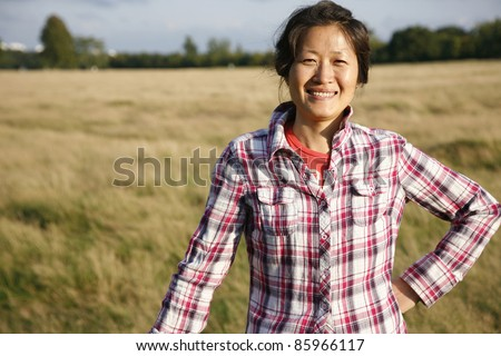 Smiling woman in Richmond Park at dusk - stock photo