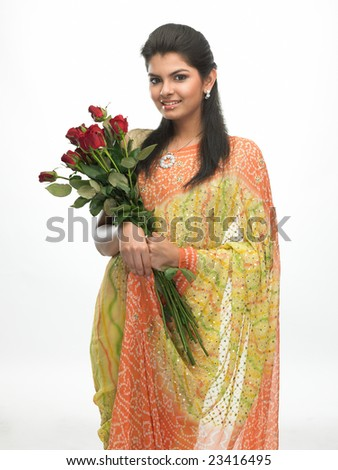 Smiling woman in sari with bunch of red roses - stock photo