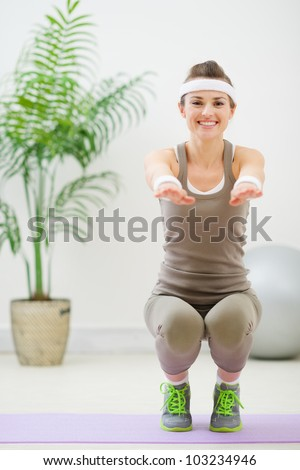 Smiling woman in sports wear squatting - stock photo