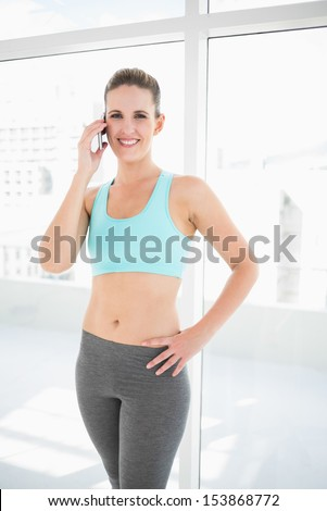 Smiling woman in sportswear talking on the phone one hand on hip looking at camera