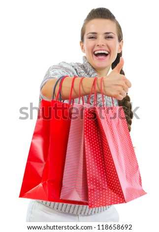 Smiling woman in sweater showing thumbs up with shopping bags - stock photo