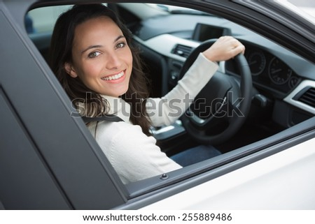 Smiling woman in the drivers seat in her car - stock photo