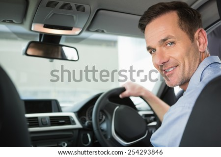 Smiling woman in the drivers seat in his car - stock photo