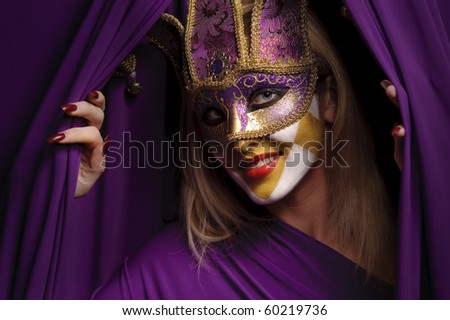 smiling woman in violet mask open curtain, may be use for theater concept - stock photo