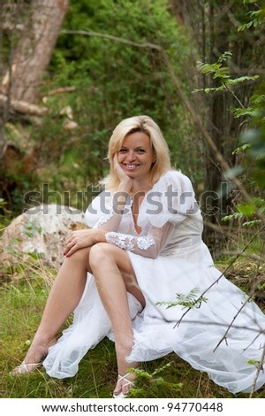 smiling woman in white dress sitting in the woods - stock photo