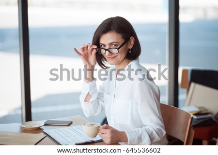 Smiling woman in white shirt sitting at table with cup of coffee and working with documents.