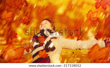 Smiling woman in winter clothes standing arms outstretched against park - stock photo