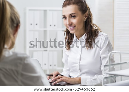 Smiling woman is looking at her colleague and typing at her laptop keyboard. Concept of office work