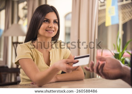 Smiling woman is paying for coffee by credit card. - stock photo