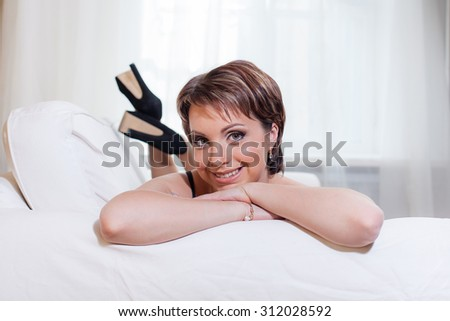 Smiling woman laying on white sofa and looking at camera