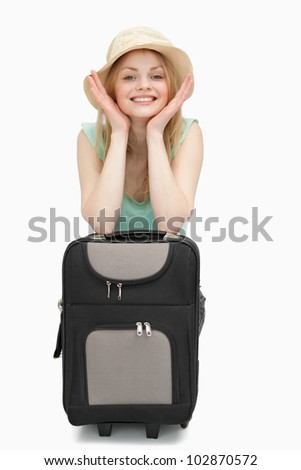 Smiling woman leaning on a suitcase while sitting against white background - stock photo
