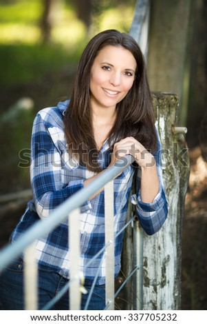Smiling woman leaning on metal gate - stock photo