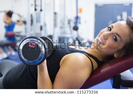 Smiling woman lifting weights in gym - stock photo